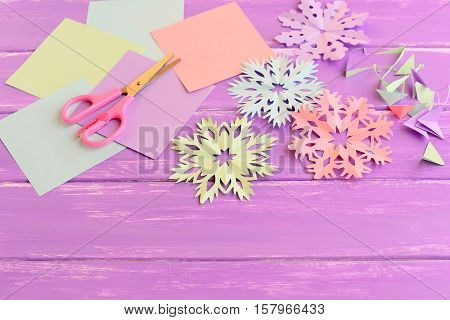 Colorful paper snowflakes, colored paper sheets and scrap, scissors on lilac wooden background. Cutting snowflakes out of colored paper. Simple winter crafts idea for children