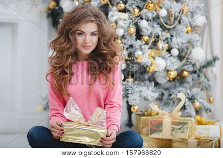 Christmas portrait of beautiful young woman with blue eyes and long curly red hair, light makeup, a beautiful smile, straight white teeth, wearing a pink t-shirt and dark blue jeans posing sitting on background of Christmas tree with gift box