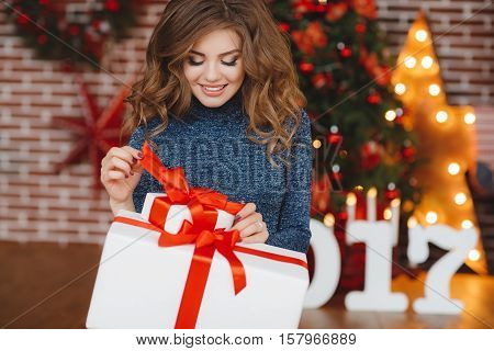 Christmas portrait of a beautiful young woman with downcast lashes,long curly red hair,light make-up,beautiful smile,even white teeth,wearing a gray sweater and dark blue jeans,sitting on a background of the Christmas tree with a white gift box