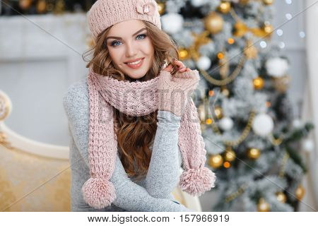 Red-haired beautiful young woman with blue eyes and curly long hair,in a beige knitted hat,scarf and gloves,beautiful makeup and large black eyelashes,purple nail Polish,posing in Studio on light background ornate Christmas tree with yellow balls