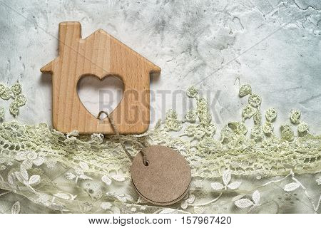 Wooden Toy House On A Cement Background With Lace Grass And Tied Blank Round Paper Tag. Copy Space F