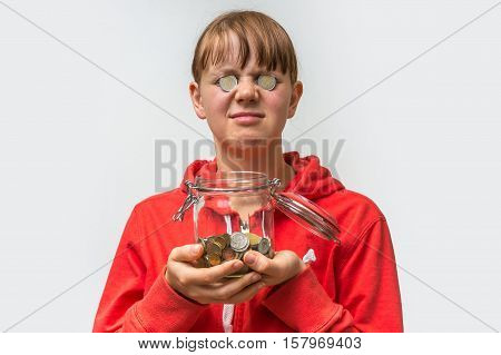 Portrait Of A Woman With Money Jar And Coins Over Her Eyes