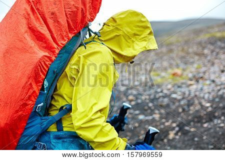 woman hiker on the trail in the Islandic mountains. Trek in National Park Landmannalaugar, Iceland. woman walking in the rain with a backpack in a raincoat and wearing a waterproof jacket