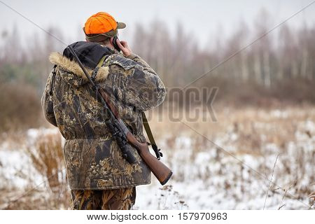 Hunter in camouflage clothes with hunting rifle and mobile phone during a winter hunting
