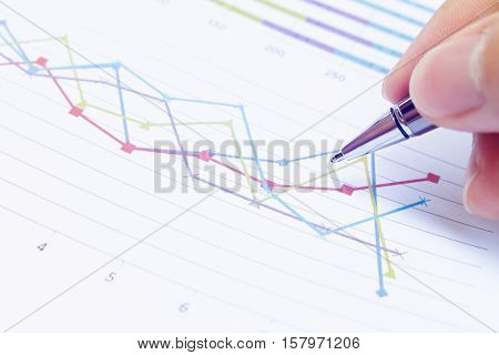 Close up Businessman hand holding pen and thinking about problem with business chart on table office.