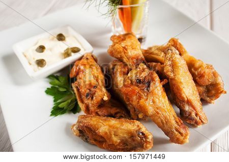 Close-up of fried chicken wings on white plate. Delicious golden grilled snacks served with creamy sauce. Junk fast food, fat concept