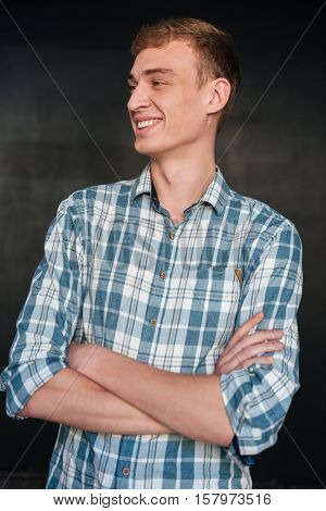 Smiling man in shirt looking away. isolated black background