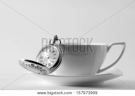 White tea cup and pocket watch closeup