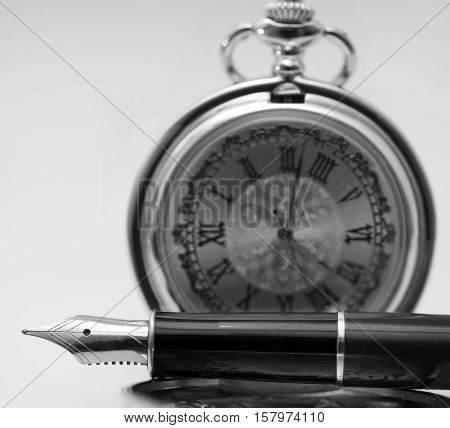 Beautiful fountain pen and pocket watch close-up