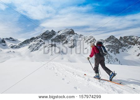 Elderly man sporting fit skis uphill climbing in te alps