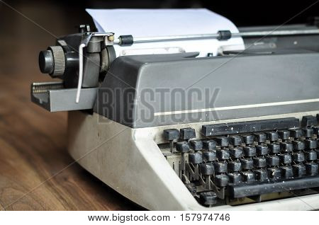 Partial close up of a typewriter with white page to add your text. The vintage typewrite is partially visible and no human face or body part are included in the image.