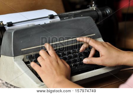 Man's hands typing on an old typewriter keyboard. A man typing on a typewriter, only hands are visible in the image.