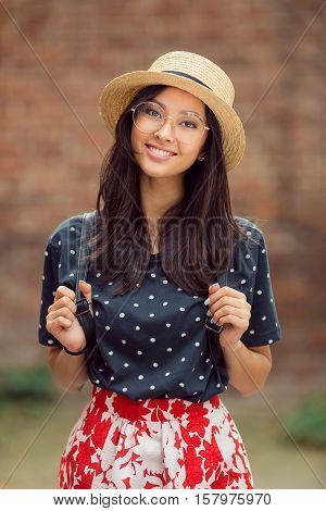 Asian student girl back to school university. Beautiful woman holding straps of backpack in autumn background. Mixed race student girl on university college campus park smiling happy and looking at camera.