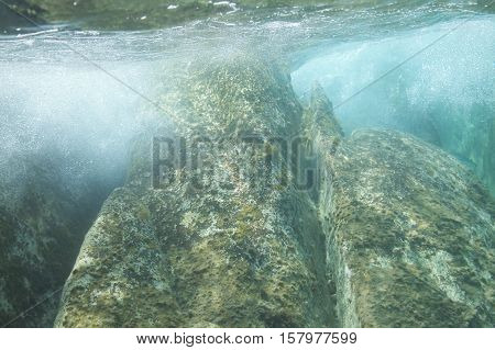 Underwater image of waves, crashed in the seashore rocks.