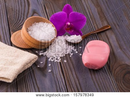 White bath salt in a wooden bowl with a spoon soap burlap and orchid on wooden table