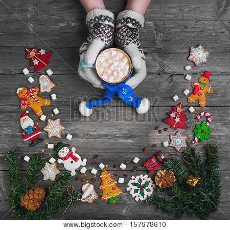 inter Christmas card. Female hands in mittens gloves cup hot chocolate (mug of cocoa) drink with marshmallow. Christmas toy on table Christmas tree. Cookies Christmas sweets. Top view blank space