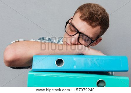 Sleepy student in glasses with folders. sleeping on the folders. isolated gray background