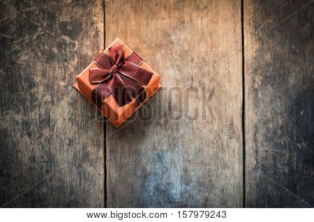 Orange colored gift box tied with scarlet bow on wooden background