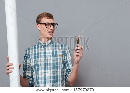 Student in glasses with Writing instruments and documents. isolated gray background