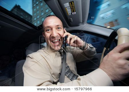 Businessman driving in car and talking on cell phone