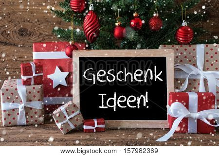 Chalkboard With German Text Geschenk Ideen Means Gift Ideas. Colorful Card For Seasons Greetings. Christmas Tree With Balls And Snowflakes. Gifts Or Presents In The Front Of Wooden Background.