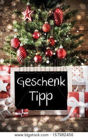 Chalkboard With German Text Geschenk Tipp Means Gift Tip. Christmas Card For Seasons Greetings. Christmas Tree With Balls. Gifts Or Presents In The Front Of Wooden Background.