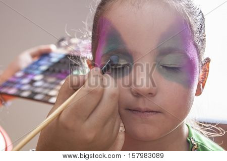 Little cute girl making facepaint before halloween party. The make-up artist is applying some colors while she closes her eyes