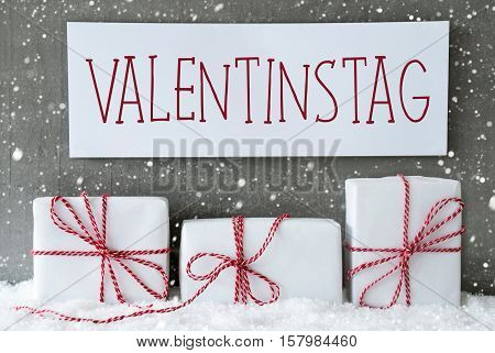 Label With German Text Valentinstag Means Valentines Day. Three Christmas Gifts Or Presents On Snow. Cement Wall As Background With Snowflakes. Modern And Urban Style.