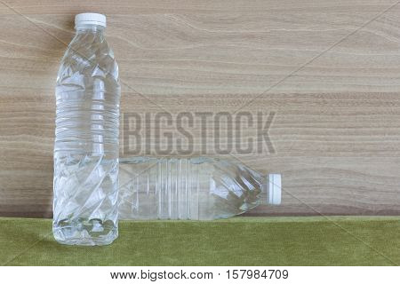 Pure water in clear bottles on green sofa wooden background.