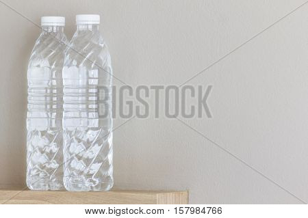 Pure water in clear bottles with gray wall background.