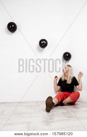 Young beautiful blonde girl with black baloons sitting on floor over white wall. Copy space
