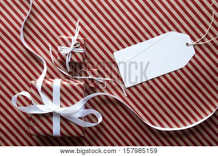 Two Gifts Or Presents With White Ribbon. Red And Brown Striped Wrapping Paper. Christmas Or Greeting Card. Label With Copy Space For Advertisement Or Your Free Text Here.
