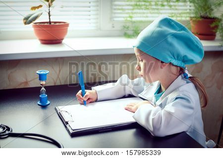 Portrait of cute little girl dressed up in doctor attire holding in her hand a clipboard and writing.