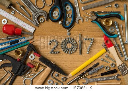 Happy new year 2017 composition with screws nails bolts dowels and tools on wooden background. New year. New year background.