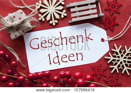 German Text Geschenk Ideen Means Gift Ideas. Christmas Decoration Like Gift Or Present, Sleigh. Card For Seasons Greetings With Red Paper Background.