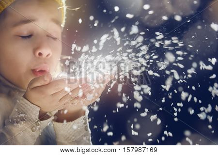 Happy child girl playing on a snowy winter walk. Little girl enjoys the game. Child girl playing outdoors in snow. Outdoor fun for winter vacation. Portrait kid on dark background.
