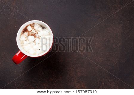 Hot chocolate with marshmallow on stone table. Top view with copy space