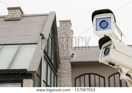 The CCTV security camera operating on luxury roof house blur background.