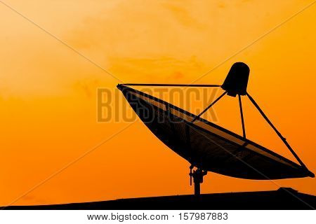 Communication satellite dish on the roof with sunset sky background. Silhouette satellite dish on orange background. Communication satellite dish silhouette with copy space background.