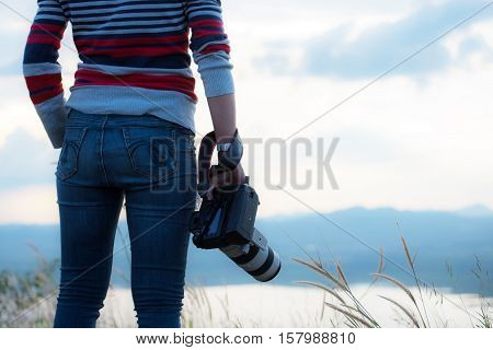 Photographer Holding Camera, Close-up. Back View, Selective Focus. Sunset  Of Background