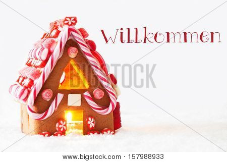 Gingerbread House In Snowy Scenery As Christmas Decoration With White Background. Candlelight For Romantic Atmosphere. German Text Willkommen Means Welcome