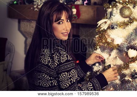 Beautiful young woman decorating a Christmas tree