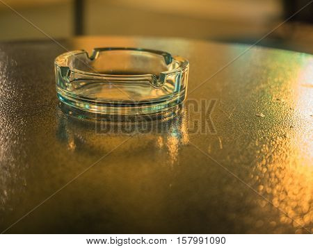 Picture of the glassy ashtray close up. Ashtray laying on the blurred surface of the table. Blurred background of the ashtray on the table. Soft focus of the table reflects yellow sunlight.