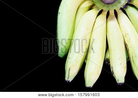 Cavendish bananas on black granite table background.