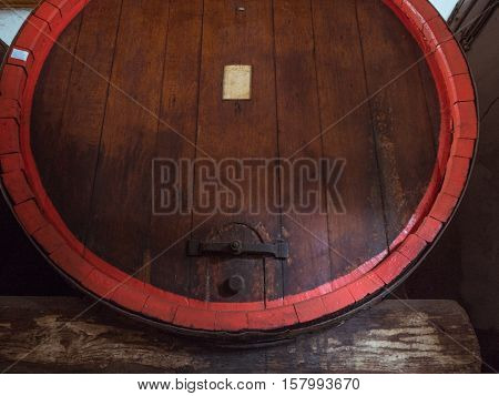 Picture of a brown wine barrel stacked in the old cellar of the winery. Background of the wooden barrel made of brown planking.