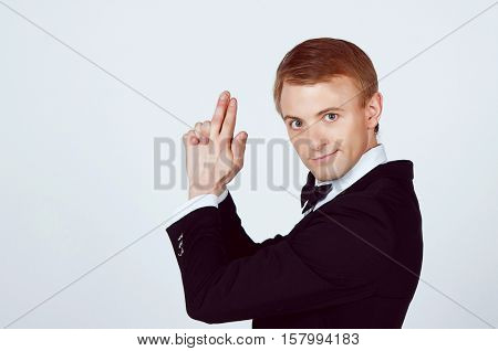 Handsome Groom joking about in Studio making a gun with his hands