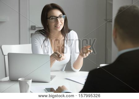 Young friendly smiling businesswoman wearing glasses talking to a male candidate at the desk, interviewing a job applicant. Rear view at a man. Business concept photo