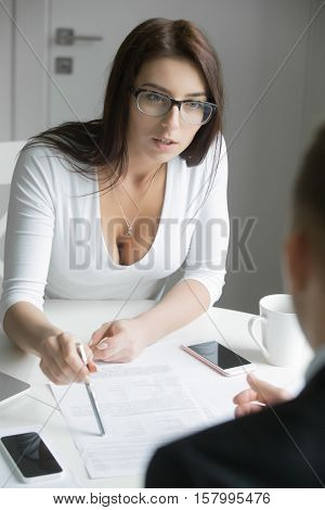 Young serious businesswoman pointing to a paper, showing a man the paragraph in a contract or portfolio. Business concept photo, view over the shoulder.