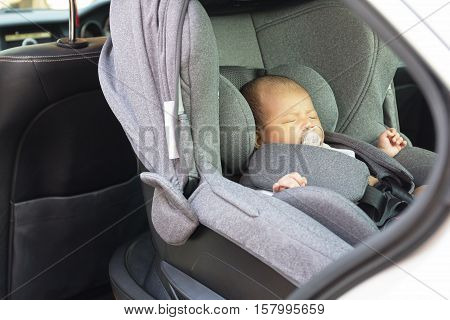 Asian cute one month old newborn baby sleeping in modern car seat. Child new born traveling safety on the road. Safe way to travel fastened seat belts in a vehicle with young kids. Trip with an infant.