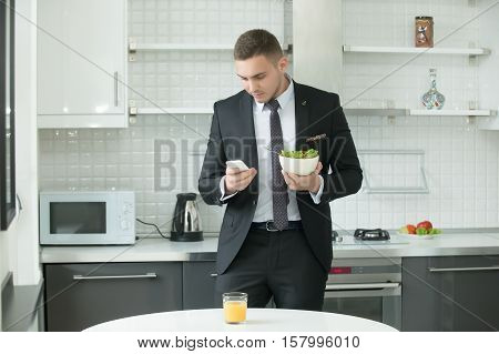 Young handsome businessman at the modern kitchen having vegan lunch, looking at his smartphone. Office worker having breakfast before working day at home